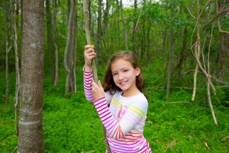 dido: Happy children girl playing in forest park jungle with liana smiling Stock Photo