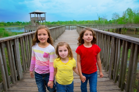 sister friends walking holding hands on lake wood smiling photo