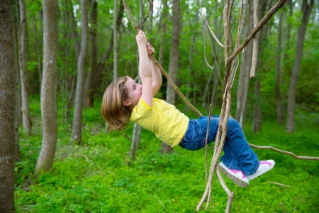 children girls playing hanging and climbing from lianas at the jungle forest park outdoor photo