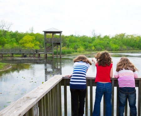 kid children girls looking and pointing at park lake in Texas rear view photo