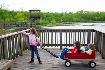 children girls looking and pointing at park lake with outdoor dump cart photo