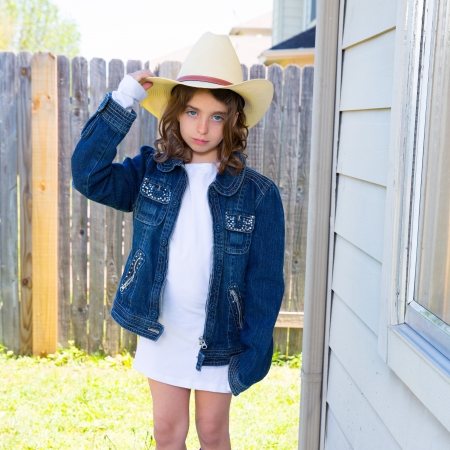 Little kid girl pretending to be a cowboy with father hat and jacket photo