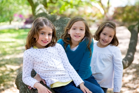 friends sister girls resting on tree trunk nature outdoor photo
