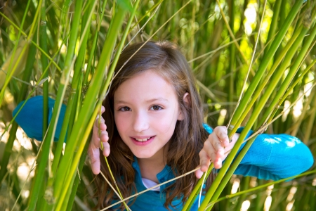 little girl surprised: beautiful little girl playing in nature  peeping from green canes