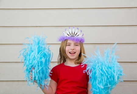 Blond kid girl playing like cheerleading pom poms with princess crown photo