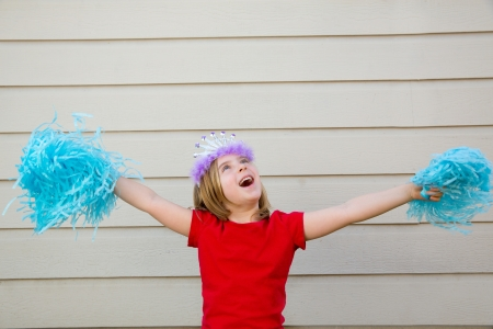 pom pom: Blond kid girl playing like cheerleading pom poms with princess crown Stock Photo