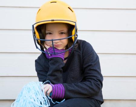 pom poms: children cheerleading pom poms girl sad relaxed yelow baseball helmet Stock Photo