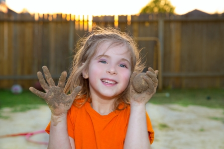 children girl playing with mud sand ball and dirty hands smiling happy photo