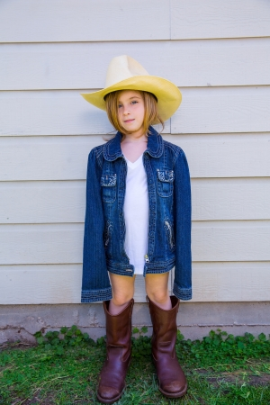 house coats: Little kid girl pretending to be a cowboy with father boots and hat Stock Photo