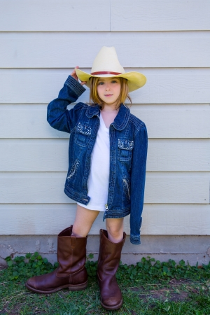 little girl posing: Little kid girl pretending to be a cowboy with father boots and hat Stock Photo