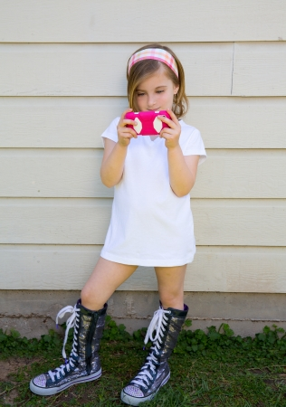 petite: blond little fashion kid girl playing with pink smartphone
