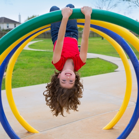 children kid girl upside down on a park playground ring game photo