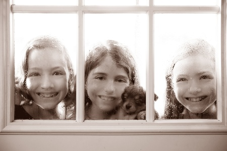 three sister friends looking through the window with a pup and raindrops photo