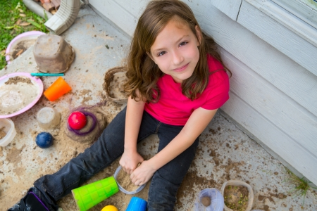 mud girl: girl playing with mud in a messy soil smiling portrait looing from high point Stock Photo