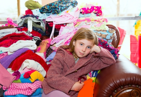 Blond kid girl sitting on a messy clothes sofa before folding laundry