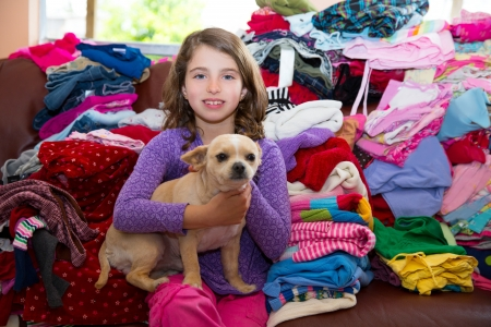 laundry pile: girl sitting on a messy clothes sofa with chihuahua dog before folding laundry