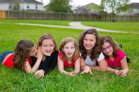 dido: Children girls group lying on lawn grass smiling happy together in a row