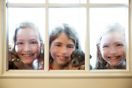 look through window: three sister friends looking through the window with a pup and raindrops Stock Photo
