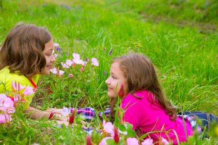 soeur jumelle: heureux filles jumelles de soeur � jouer couch� sur des fleurs de printemps prairie