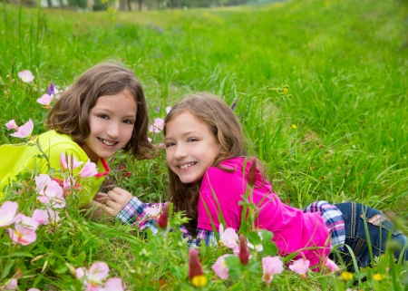 dido: happy twin sister girls playing lying on spring flowers meadow Stock Photo