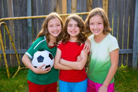 smiling girls: three sister girls friends soccer football winner players on the backyard