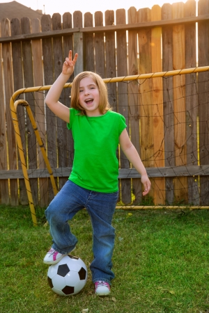 Blond little girl soccer player happy in backyard with ball photo