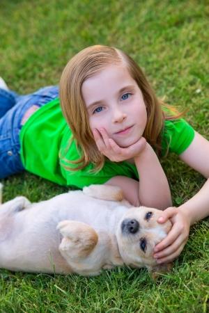 miniature breed: Feliz niña rubia con su perrito chihuahua retrato tumbado en el césped Foto de archivo