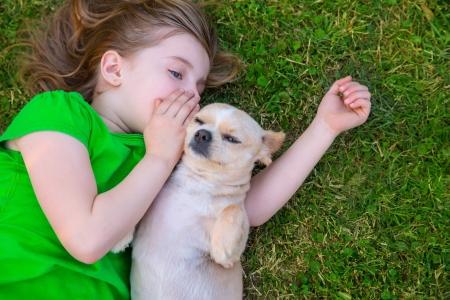 Blond gelukkig meisje met haar chihuahua hondje portret liggend op het gazon Stockfoto