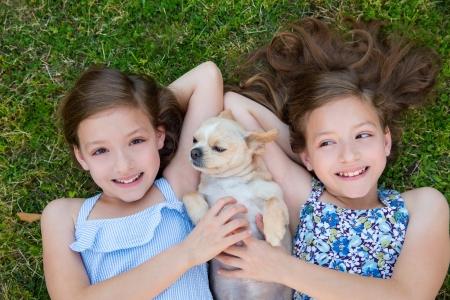 niñas gemelas: hermanas gemelas jugando con el perro chihuahua que miente en c?sped del patio trasero Foto de archivo