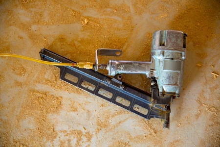 embed: Air nail gun pneumatic framing nailer on grunge sawdust floor while house contstuction