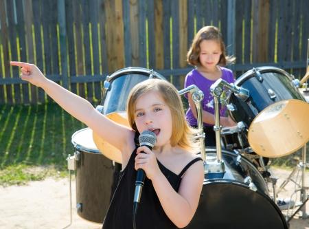 personas cantando: Rubio chico cantante chica cantando banda tocando en directo en concierto patio con amigos