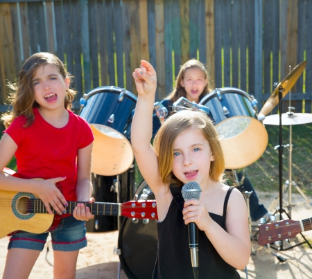 playing music: Blond kid singer girl singing playing live band in backyard concert with friends