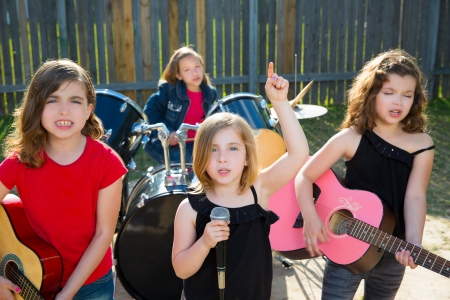 Blond kid singer girl singing playing live band in backyard concert with friends photo