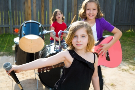child singing: Blond kid singer girl singing playing live band in backyard concert with friends