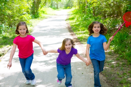american butterflies: Friends and sister girls running in the forest track smiling happy with butterfly net Stock Photo