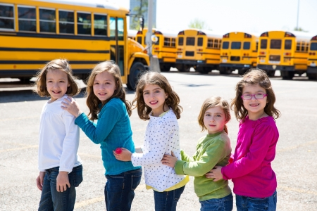 school girls friends sisters in a row walking from yellow school bus lot photo