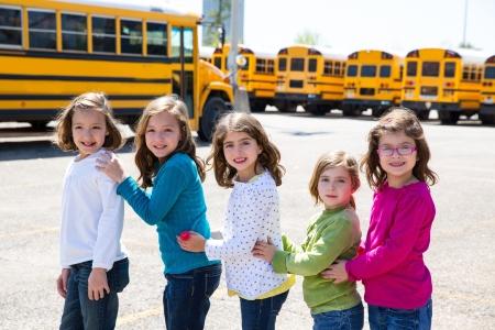 team journey: school girls friends sisters in a row walking from yellow school bus lot Stock Photo