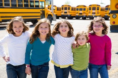 school girls friends sisters in a row walking from yellow school bus lot photo