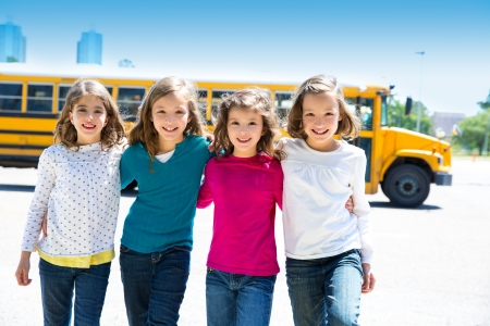 sister: school girls friends sisters in a row walking from yellow school bus lot Stock Photo