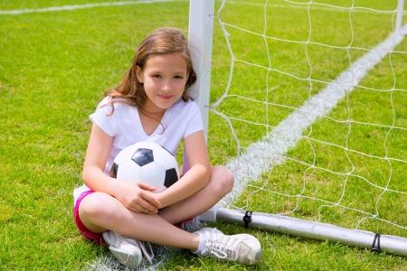 arquero futbol: Balompi� muchacha ni�o relajado en el c�sped de la hierba con la bola Foto de archivo