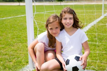 ni�as jugando: F�tbol f�tbol muchachas del cabrito juegan en el campo de deportes al aire libre Foto de archivo
