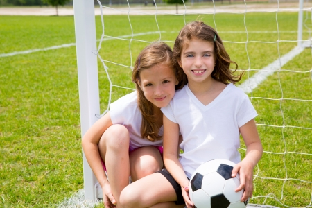 little girl sitting: Soccer football kid girls playing on sports outdoor field Stock Photo