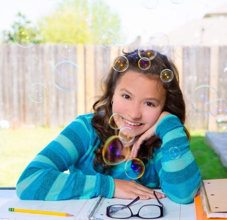 glass fence: American latin teen girl with soap bubbles doing homework on backyard Stock Photo