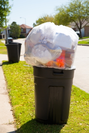 Trash bin dustbin full of excess garbage on street lawn photo