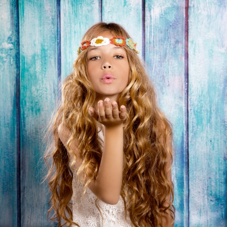 Blond hippie children girl blowing mouth with hand on blue grunge wood photo