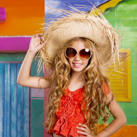 blond children happy tourist girl with straw beach hat and sunglasses on a tropical house photo