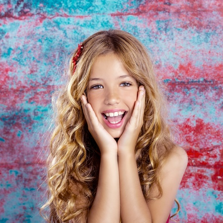 Blond kid girl happy smiling expression hands in face gesture photo