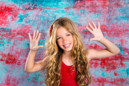 Blond happy children girl in red happy with arms up in grunge background photo