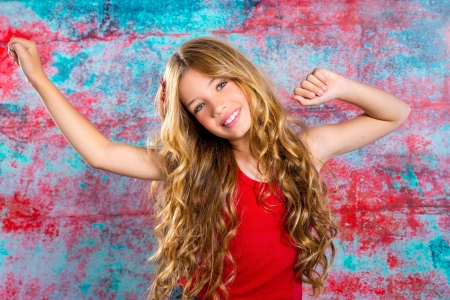 Blond happy kid girl in red happy with arms up in grunge background photo