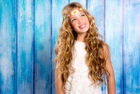 Blond happy hippie children girl smiling on blue grunge wood background photo